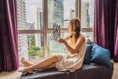 A mulher senta-se pela janela e usa-se uma escova de cabelo eletrônica fotografia de stock royalty free