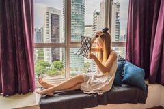 A mulher senta-se pela janela e usa-se uma escova de cabelo eletrônica imagem de stock
