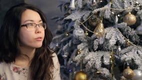 A mulher senta-se perto da árvore de Natal, bebendo o chá falando dentro video estoque