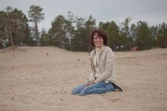 Mulher sentada na praia na chuva Fotografia de Stock Royalty Free