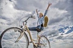 A mulher sente feliz quando aprecie dar um ciclo A menina monta o fundo do c?u da bicicleta Como mudan?as de ciclagem sua vida e  fotos de stock