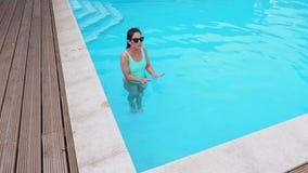 A mulher sente o frio na água do ` s da associação vídeos de arquivo