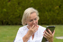 Mulher sereno superior que usa um PC preto da tabuleta imagem de stock