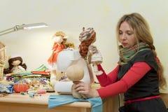 A mulher sews bonecas Fotos de Stock Royalty Free