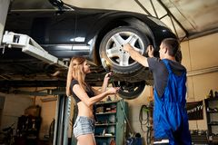 A mulher 'sexy' ajuda o carro do reparo do auto mecânico no elevador hidráulico fotografia de stock royalty free