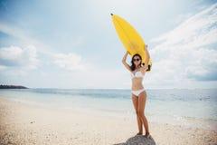 Mulher 'sexy' bonita feliz saudável com a prancha que tem o divertimento pelo mar no fundo do céu azul Lazer ativo do estilo de v imagem de stock