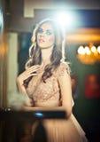 Mulher 'sexy' bonita no vestido do laço do nude que levanta no cenário do vintage com luzes brilhantes Imagens de Stock Royalty Free