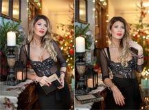 Mulher 'sexy' bonita no vestido preto elegante com a árvore do Xmas no fundo Retrato da menina loura elegante que guarda um livro Fotos de Stock Royalty Free