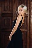 Mulher 'sexy' bonita nova em um vestido preto elegante longo luxuoso, em uma composição na moda e em brincos à moda Blonde seduto Imagens de Stock Royalty Free