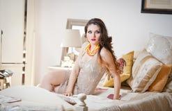 Mulher 'sexy' bonita nova no vestido apertado curto branco que levanta o desafio interno na cama do vintage Morena longa sensual  Fotografia de Stock