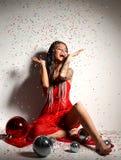 Mulher 'sexy' bonita nova no vestido vermelho elegante que senta-se na coroa do ouro com a bola e os confetes da decoração do Nat Imagem de Stock Royalty Free