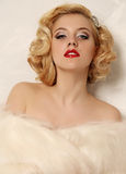 A mulher 'sexy' com cabelo encaracolado louro e composição brilhante, veste a pele Fotos de Stock Royalty Free