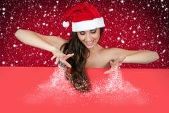 Mulher 'sexy' de Santa que polvilha a neve a bordo Fotografia de Stock Royalty Free