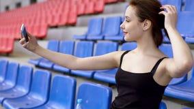 A mulher 'sexy' do ajuste toma a foto dsi mesma em uma tribuna do estádio filme