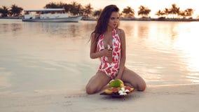 Mulher 'sexy' do biquini com bacia de frutos que aprecia o por do sol bonito na praia tropical O modelo moreno com cabelo ondulad foto de stock