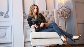 Mulher 'sexy' do cabelo do marrom da forma que senta-se em calças de brim luxuosas do casaco de cabedal e da sarja de Nimes da po vídeos de arquivo