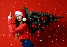 Mulher 'sexy' do esporte da aptidão do Natal que veste o chapéu de Santa que guarda a árvore do xmas em seus ombros Flocos de nev imagem de stock royalty free