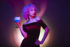 Mulher 'sexy' e misteriosa que bebe um isolat azul da bebida alcoólica Fotografia de Stock Royalty Free