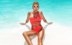 A mulher 'sexy' elegante no biquini no corpo magro e escultural sol-bronzeado est? levantando perto da piscina Tomar sol pela pis fotos de stock royalty free