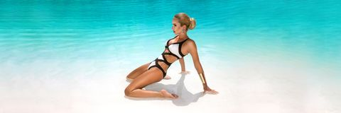A mulher 'sexy' elegante no biquini luxuoso no corpo magro e escultural sol-bronzeado está levantando perto da piscina Tomar sol  fotografia de stock royalty free