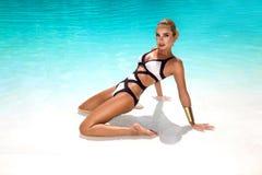 A mulher 'sexy' elegante no biquini luxuoso no corpo magro e escultural sol-bronzeado está levantando perto da piscina Tomar sol  imagem de stock royalty free