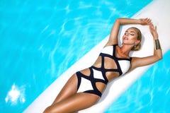 A mulher 'sexy' elegante no biquini luxuoso no corpo magro e escultural sol-bronzeado está levantando perto da piscina Tomar sol  foto de stock