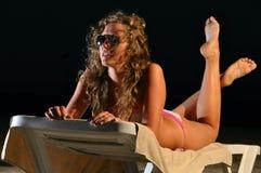 A mulher 'sexy' está encontrando-se na praia da noite imagem de stock