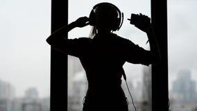 Mulher 'sexy', feliz que escutam a música e dança