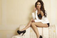 Mulher 'sexy' magro nova no revestimento contra o sofá Imagem de Stock