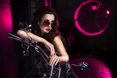 Mulher 'sexy' moreno no roupa interior, nos saltos e em óculos de sol pretos no estúdio na luz vermelha em uma motocicleta dentro Fotos de Stock Royalty Free