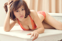 Mulher 'sexy' na roupa interior que groveling na tabela Fotografia de Stock Royalty Free