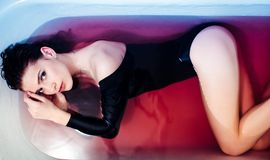 Mulher 'sexy' no bodysuit no banho Luz brilhante e água colorida Ombros desencapados fotos de stock