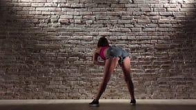 A mulher 'sexy' no short da parte superior e da sarja de Nimes da colheita dança o twerk contra uma parede de tijolo Movimento le video estoque