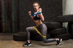 Mulher 'sexy' no sportswear usando uma faixa da resist?ncia em sua rotina do exerc?cio A jovem mulher executa exercícios da aptid imagem de stock