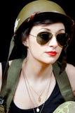 Mulher 'sexy' no uniforme militar que levanta contra o fundo preto Fotos de Stock