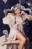 Mulher 'sexy' no vestido de seda bege que senta-se na poltrona preta Imagem de Stock