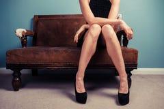 Mulher 'sexy' nos saltos no sofá Fotografia de Stock