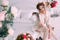 Mulher 'sexy' nova bonita que senta-se na cama branca, vestido branco vestindo do laço, cabelo decorado com flores Composição per Foto de Stock Royalty Free