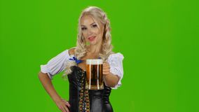 Mulher 'sexy' nova de Oktoberfest canecas de cerveja bávaras tradicionais vestindo do serviço do dirndl do vestido Tela verde filme