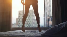Mulher 'sexy' nova feliz que salta na cama no apartamento luxuoso no tempo do por do sol perca acima fotos de stock royalty free
