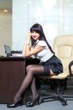 Mulher 'sexy' nova nas meias pretas que sentam-se no local de trabalho dentro fora Imagem de Stock Royalty Free