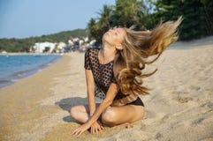 A mulher 'sexy' nova que coloca e amaciada próximo, une-se no bom dia quente das férias de verão, vestindo uma camiseta preta no  Fotos de Stock Royalty Free