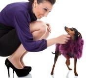 Mulher 'sexy' que dobra com seu cão extravagante Foto de Stock