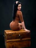 Mulher 'sexy' que senta-se em uma caixa de madeira imagem de stock