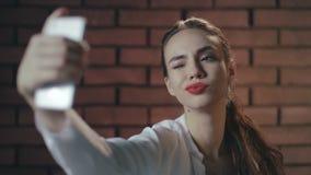 Mulher 'sexy' que usa o telefone celular para a foto do selfie no fundo da parede de tijolo vídeos de arquivo