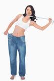 Mulher 'sexy' que veste calças demasiado grandes e que estrangula-se com mea Fotos de Stock Royalty Free