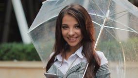 A mulher smilling nova está com o guarda-chuva em sua mão na rua e a vista na câmera Guarda vídeos de arquivo
