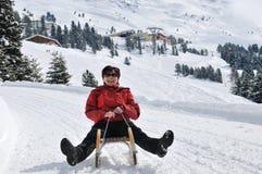 Mulher sênior no sledge que tem o divertimento Fotografia de Stock