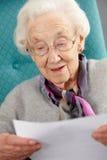 Mulher sênior que relaxa na letra da leitura da cadeira Fotos de Stock