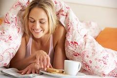 Mulher sob o Duvet que come o pequeno almoço Fotografia de Stock Royalty Free